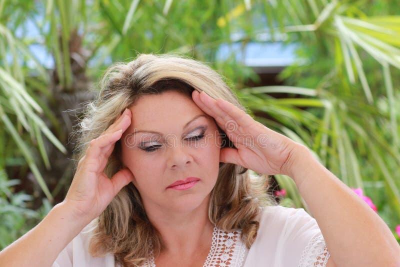 Kvinna med den stränga migrän som rymmer hennes huvud royaltyfria foton
