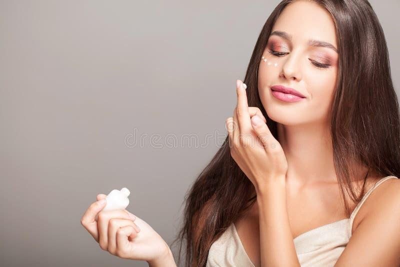 Kvinna med den sunda framsidan som applicerar skönhetsmedelkräm under ögonen arkivfoton