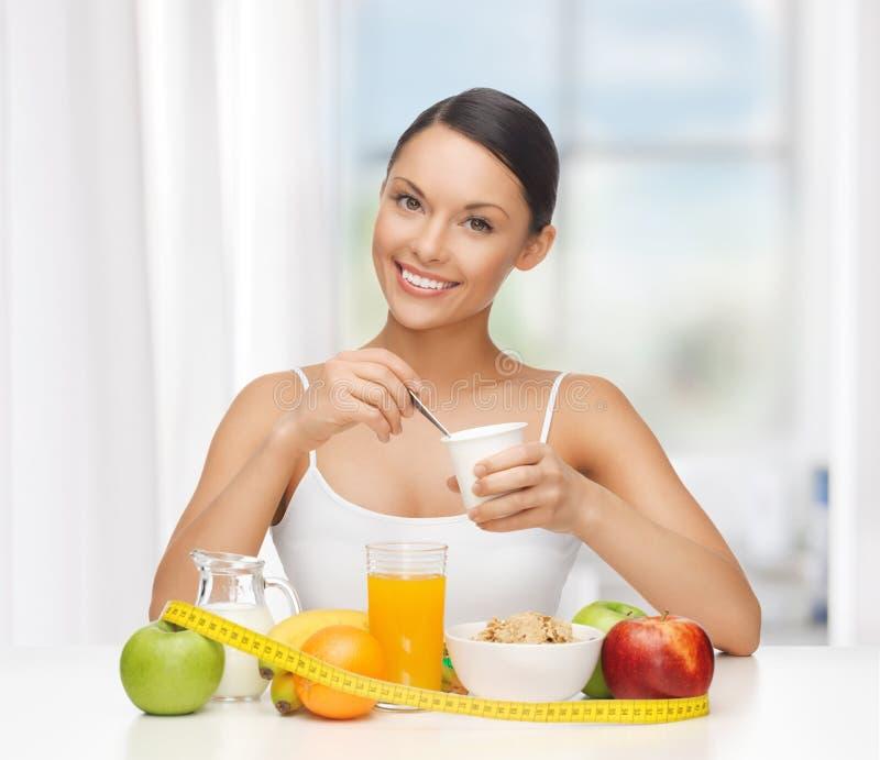 Kvinna med den sunda frukosten och mätabandet royaltyfria bilder