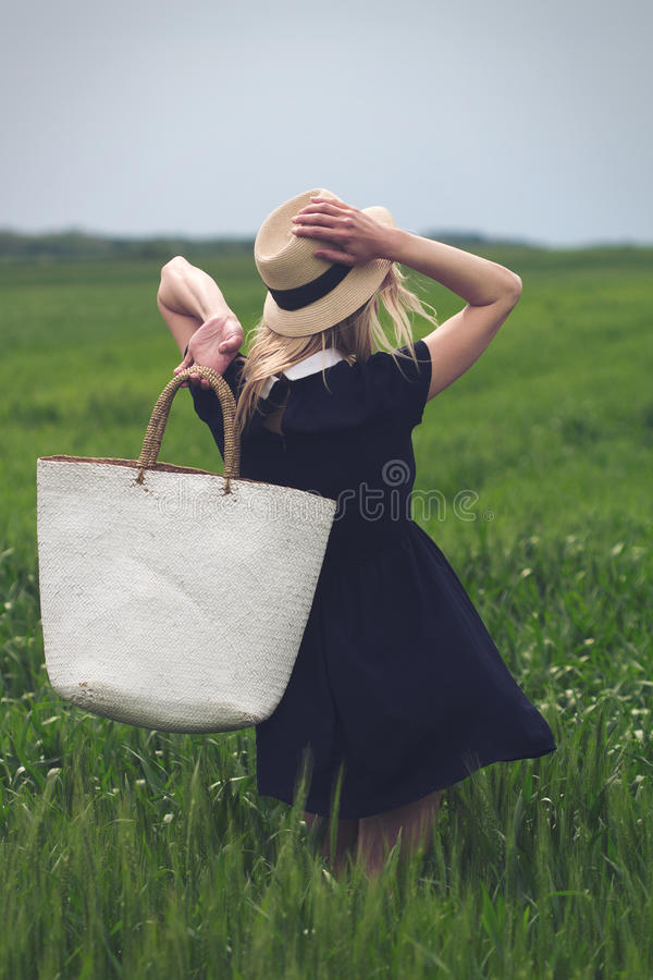 Kvinna med den svarta klänningen i ett fält av grönt vete fotografering för bildbyråer