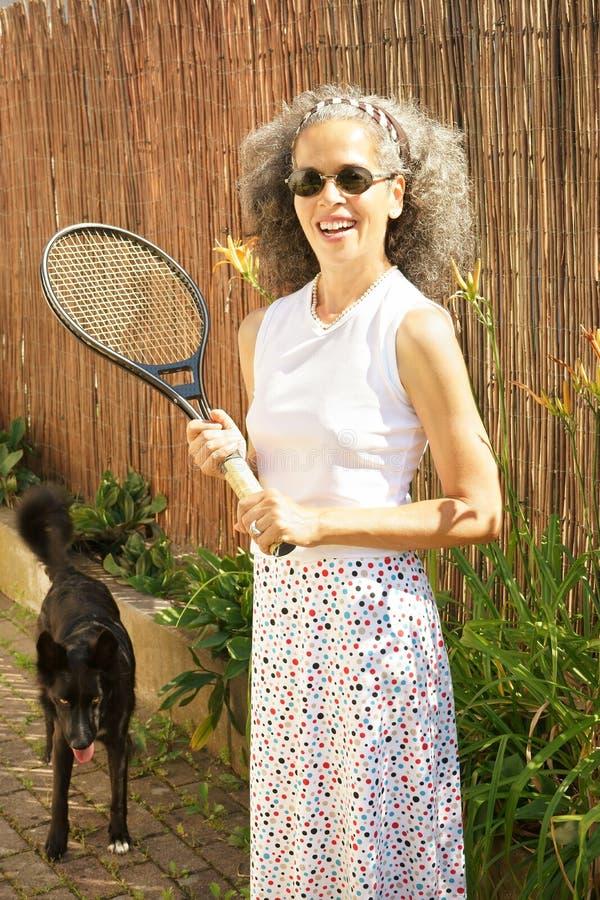 Kvinna med den tennisracket och hunden arkivbilder