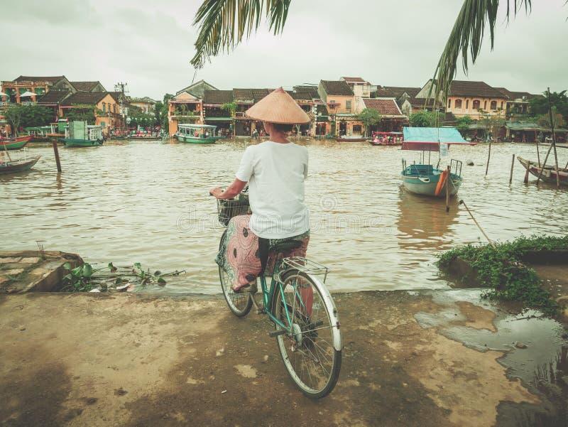 Kvinna med den traditionella vietnamesiska hatten som cyklar på flodbanken på Hoi An, berömd loppdestination i Vietnam Flod?versv arkivfoton