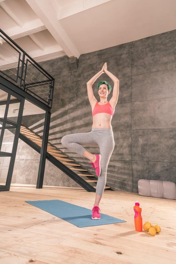 Kvinna med den trevliga kroppen som bär grå damasker, medan göra yoga royaltyfria foton