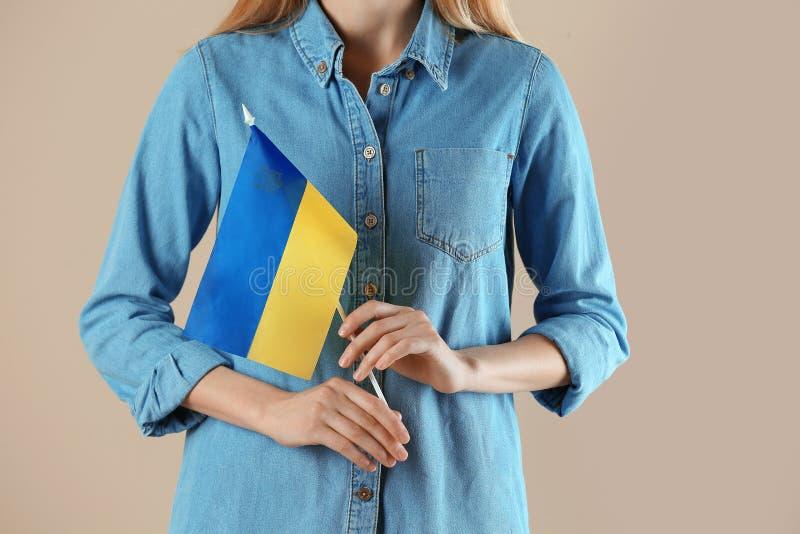 Kvinna med den ukrainska flaggan mot f?rgbakgrund arkivfoton