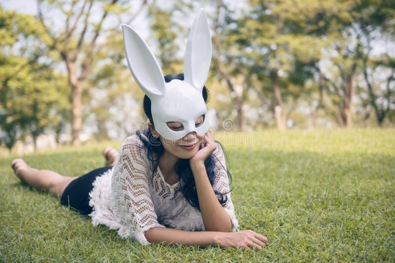 kvinna med den vita kaninmaskeringen i trädgård royaltyfria bilder