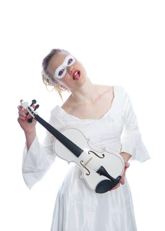 Kvinna med den vita partimaskeringen på framsida- och vitfiolen i händer arkivfoton