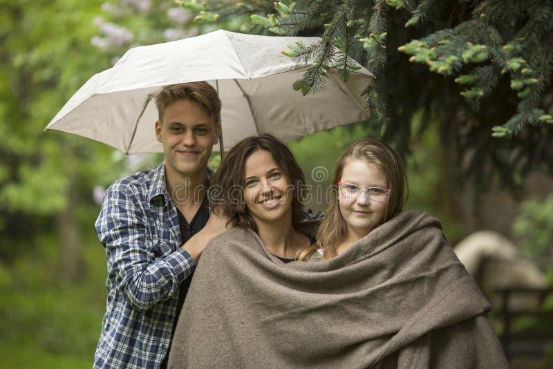 Kvinna med deras vuxna barn, dotter och son, i parkera under ett paraply Lyckligt royaltyfria bilder