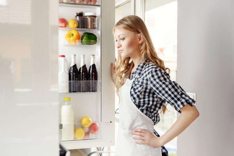 Kvinna med det öppna kylskåpet royaltyfria foton