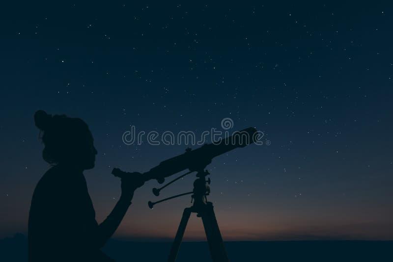 Kvinna med det astronomiska teleskopet Konstellationer för stjärnklar natt, royaltyfri bild