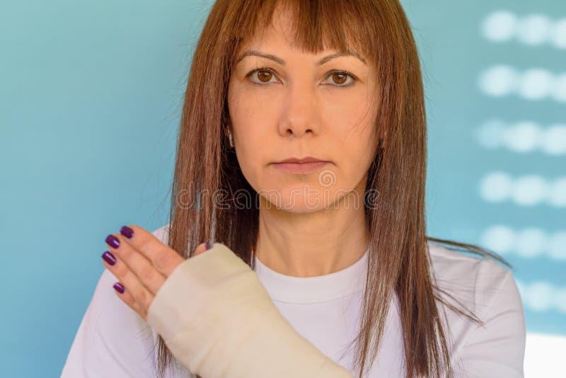 Kvinna med det brutna armbenet i ensemblen, packad hand på blå bakgrund royaltyfri fotografi
