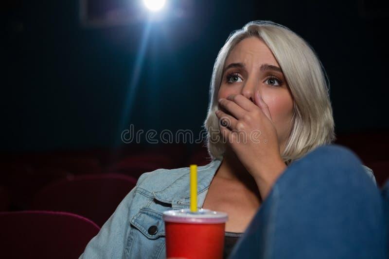 Kvinna med det chockade uttryckt som ser filmen arkivbild