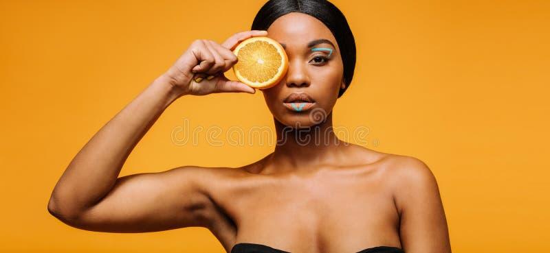 Kvinna med det konstnärliga sminket som rymmer en apelsin royaltyfri bild