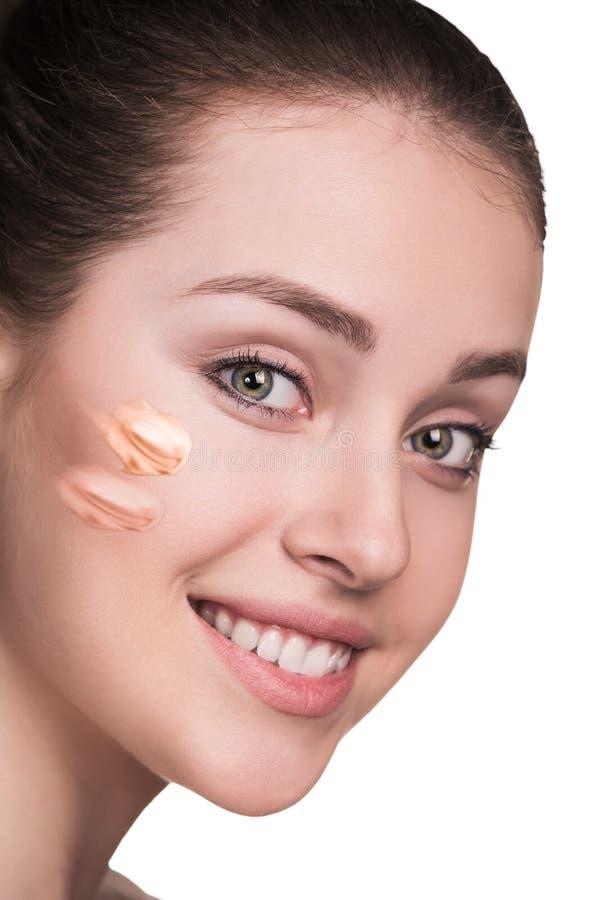 Kvinna med det kosmetiska fundamentet på hud arkivbild