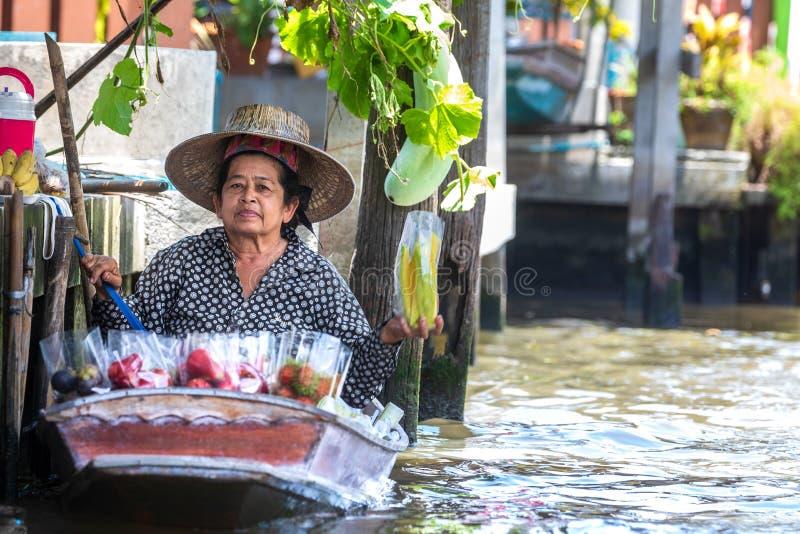 Kvinna med det lilla fartyget i den sväva marknaden i den Damnoen floden i Thailand royaltyfria bilder