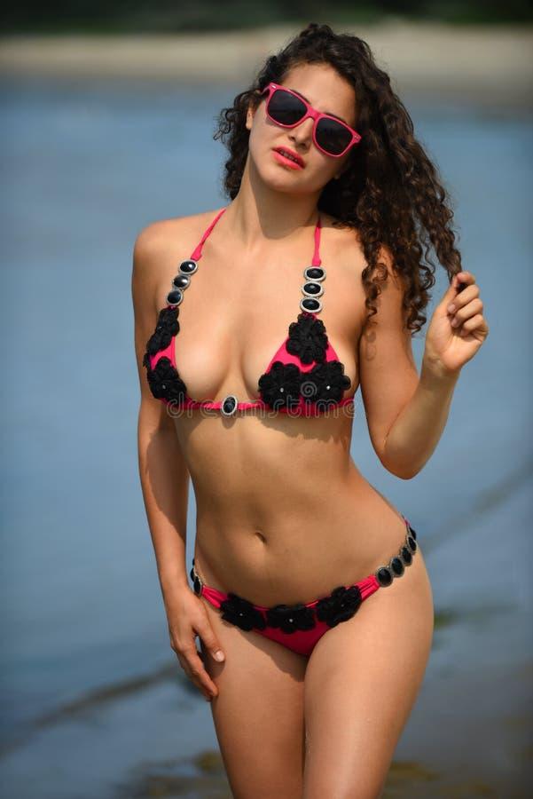 Kvinna med det perfekta curvy diagramet posera som är sexigt på stranden arkivbilder