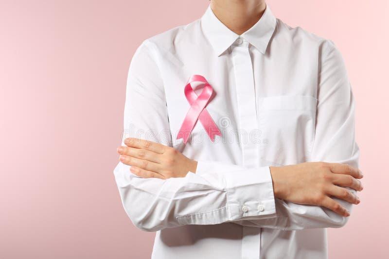Kvinna med det rosa bandet mot färgbakgrund, closeup Rosa band p? corkboard royaltyfri fotografi