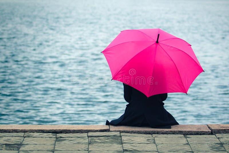 Kvinna med det rosa paraplyet arkivbild