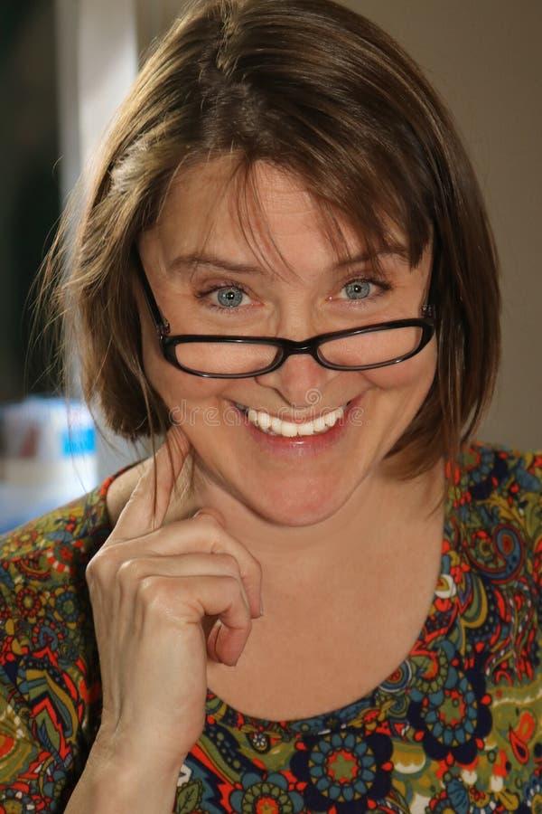 Kvinna med det stora leendet som ser över hennes läs- exponeringsglas - brunetthår och stora blåa ögon royaltyfri fotografi