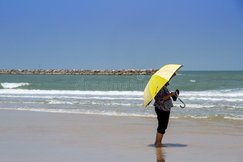 Kvinna med det stora paraplyet som väntar på någon på stranden arkivbilder