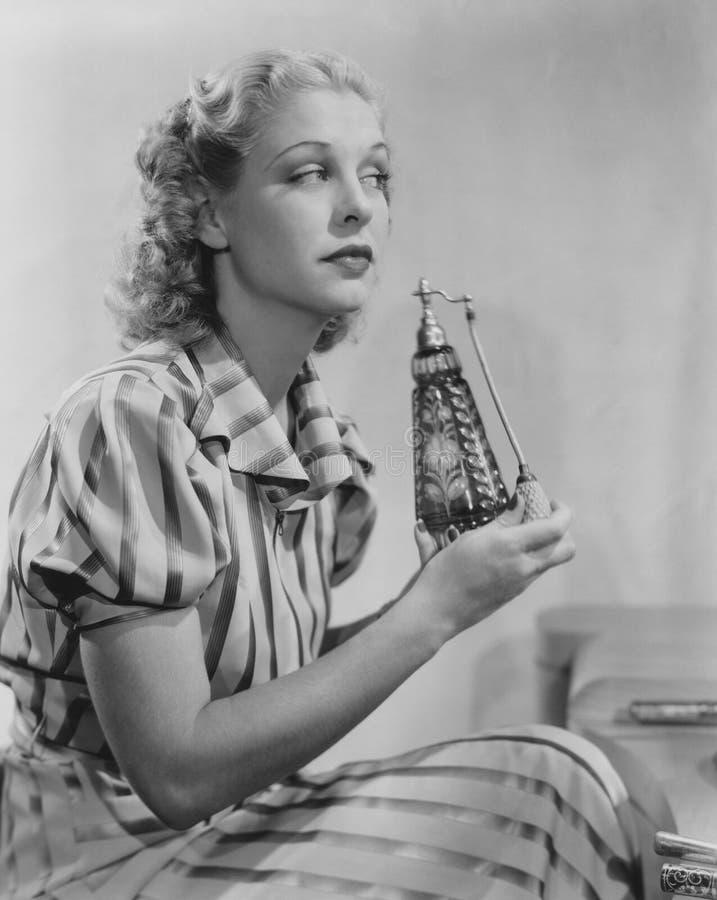 Kvinna med doftsprejflaskan fotografering för bildbyråer