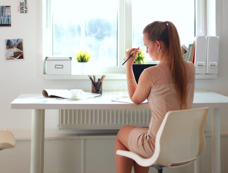 Kvinna med dokument som sitter på skrivbordet och bärbara datorn arkivfoto