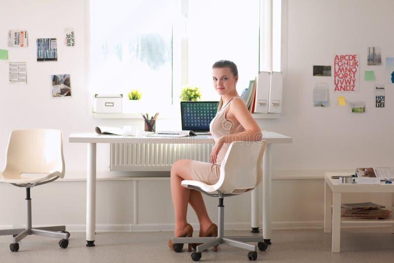 Kvinna med dokument som sitter på skrivbordet och bärbara datorn royaltyfria foton