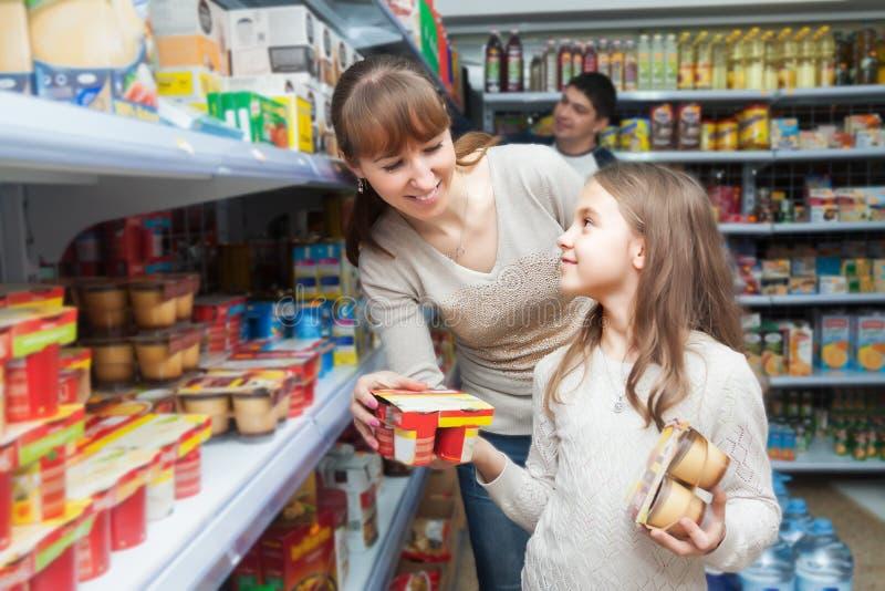 Kvinna med dotterköpandeyoghurter arkivbilder
