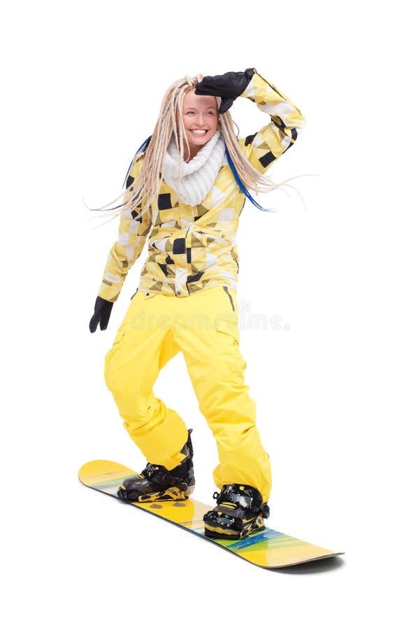 Kvinna med dreadlocks som står på snowboard arkivbilder