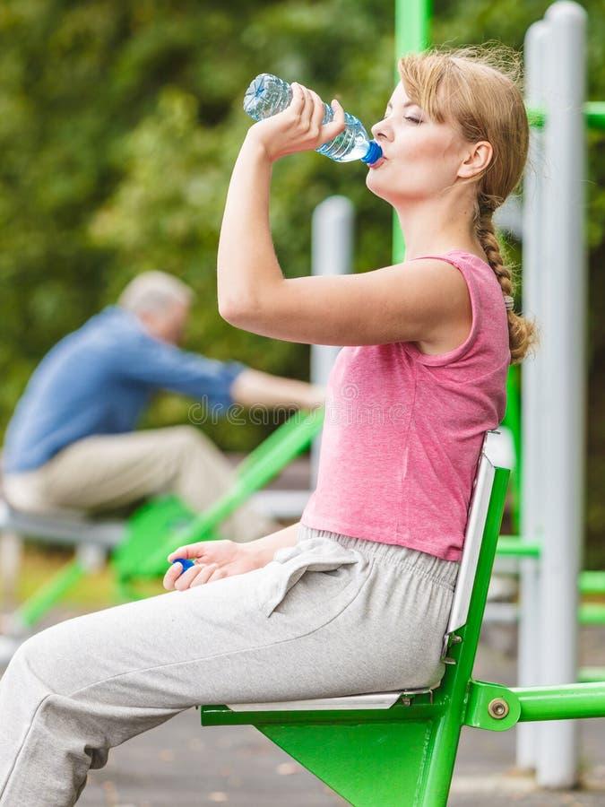 Kvinna med dricksvatten som tar avbrottet Kondition arkivbild