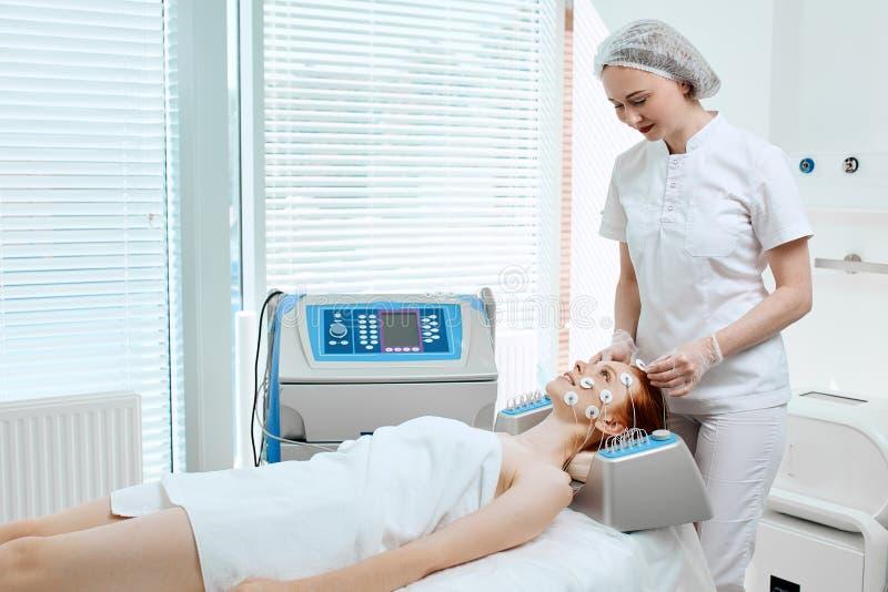 Kvinna med elektroder på hennes framsida som mottar elektrisk stimulans på hennes hud arkivfoton