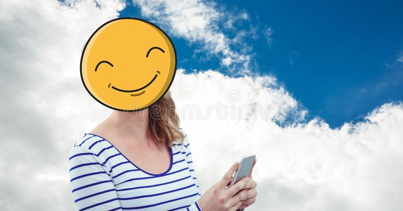 Kvinna med emoji över framsida genom att använda den smarta telefonen mot himmel royaltyfri illustrationer