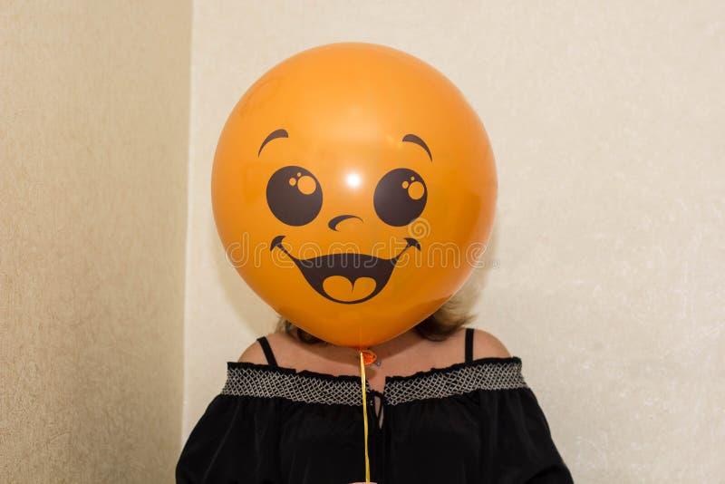 kvinna med en ballong på hans huvud med smileyframsidan arkivbild