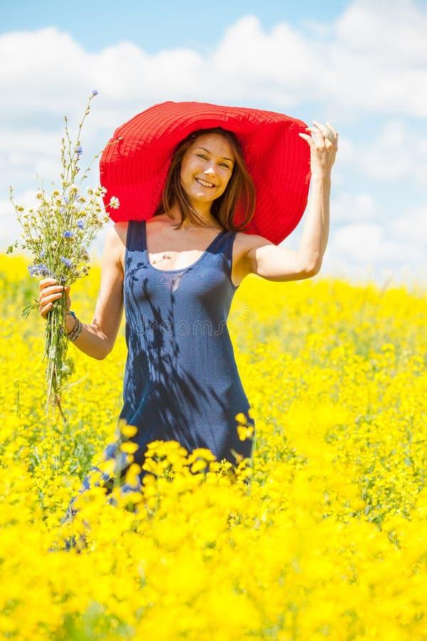 Kvinna med en bukett i en röd hatt på en solig dag under wildflow arkivfoton