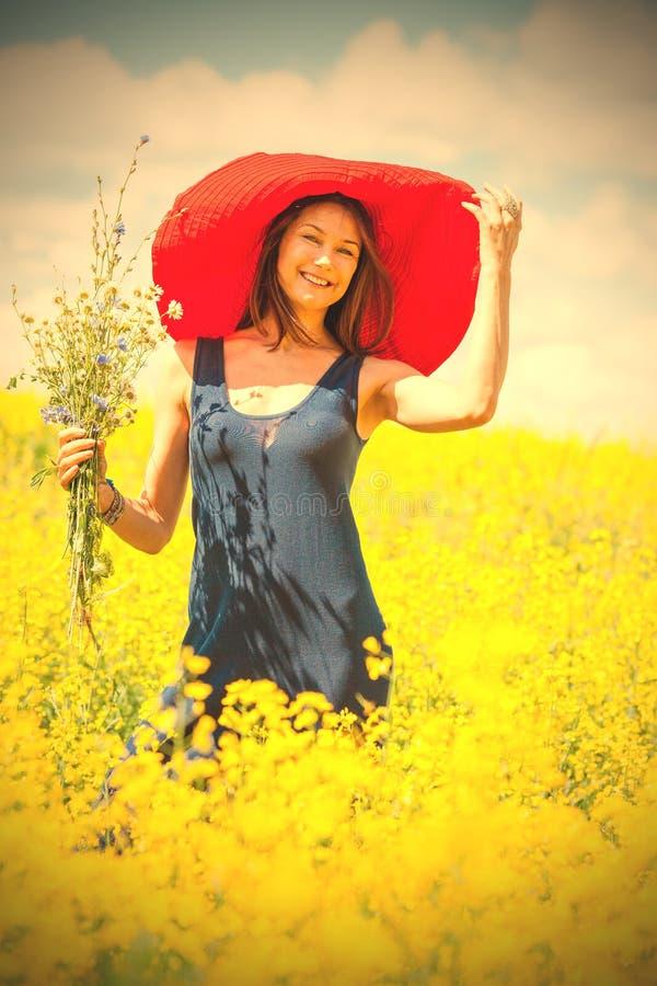 Kvinna med en bukett i en röd hatt på en solig dag under wildflow arkivbilder