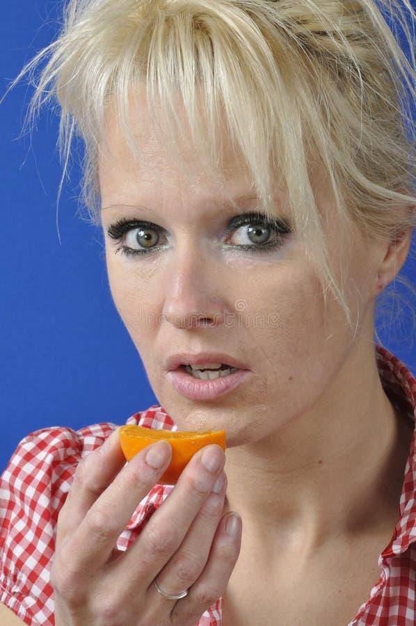 Kvinna med en clementine royaltyfri foto
