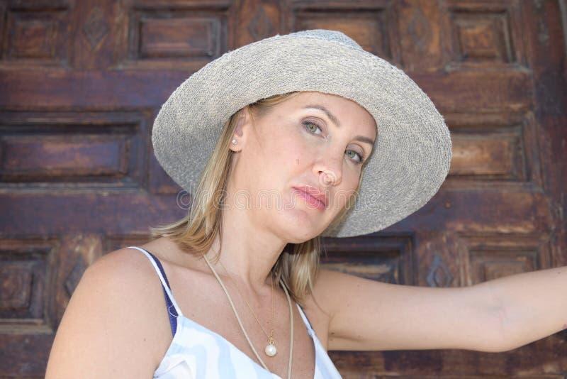 Kvinna med en hatt som in ser kameran av en lantlig brun trädörr i sommar arkivfoto