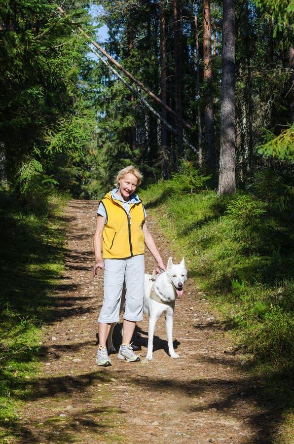 Kvinna med en hund på en gå i parkera royaltyfria foton