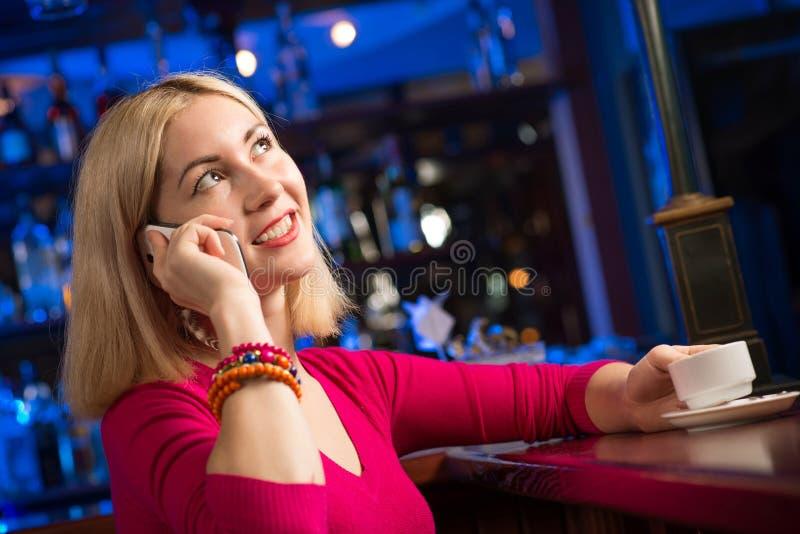 Kvinna med en kopp kaffe och en mobiltelefon royaltyfri bild