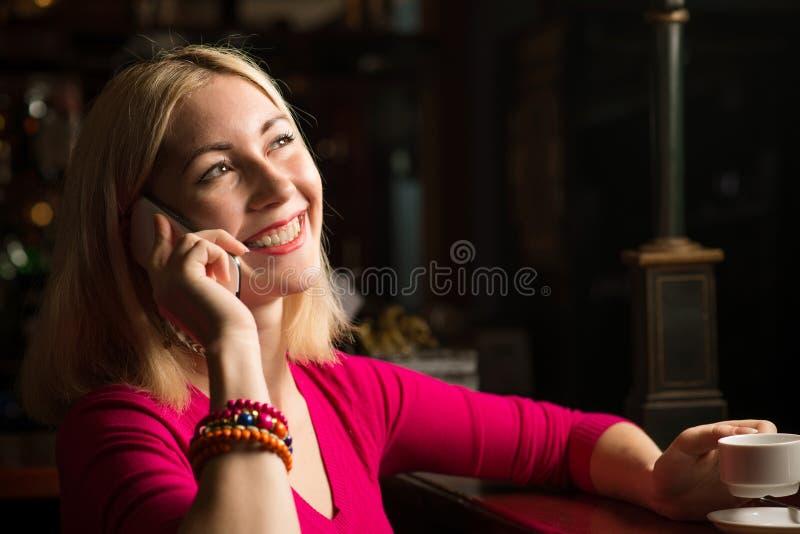 Kvinna med en kopp kaffe och en mobiltelefon royaltyfria bilder