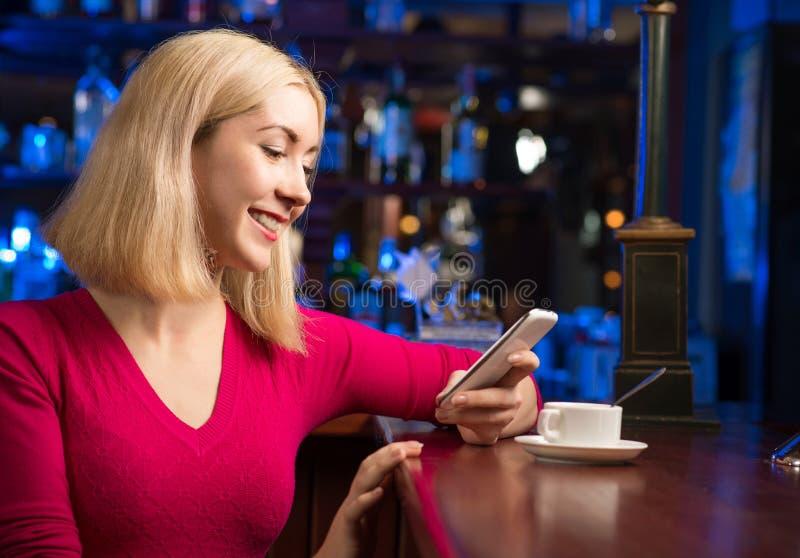 Kvinna med en kopp kaffe och en mobiltelefon royaltyfri foto