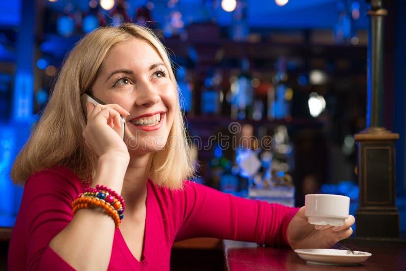 Kvinna med en kopp kaffe och en mobiltelefon arkivbild