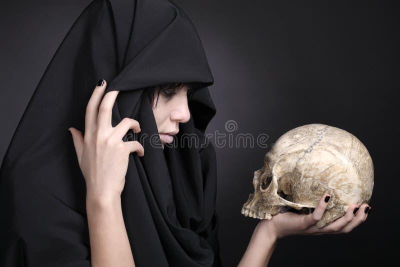 Kvinna med en mänsklig skalle i black royaltyfri foto