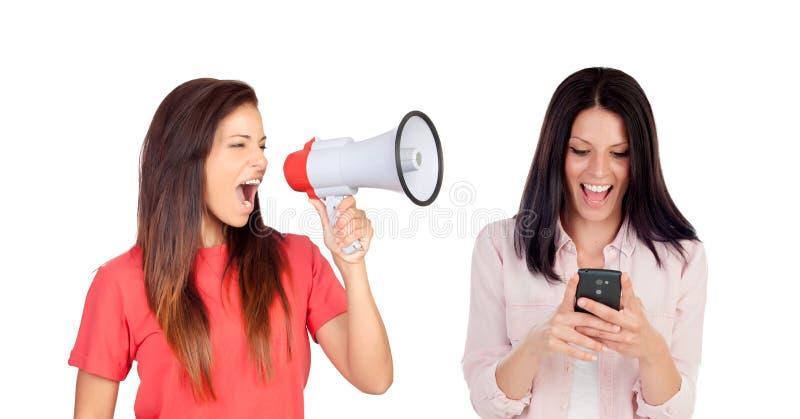 Kvinna med en megafon som ropar hennes vän med en mobil royaltyfria bilder