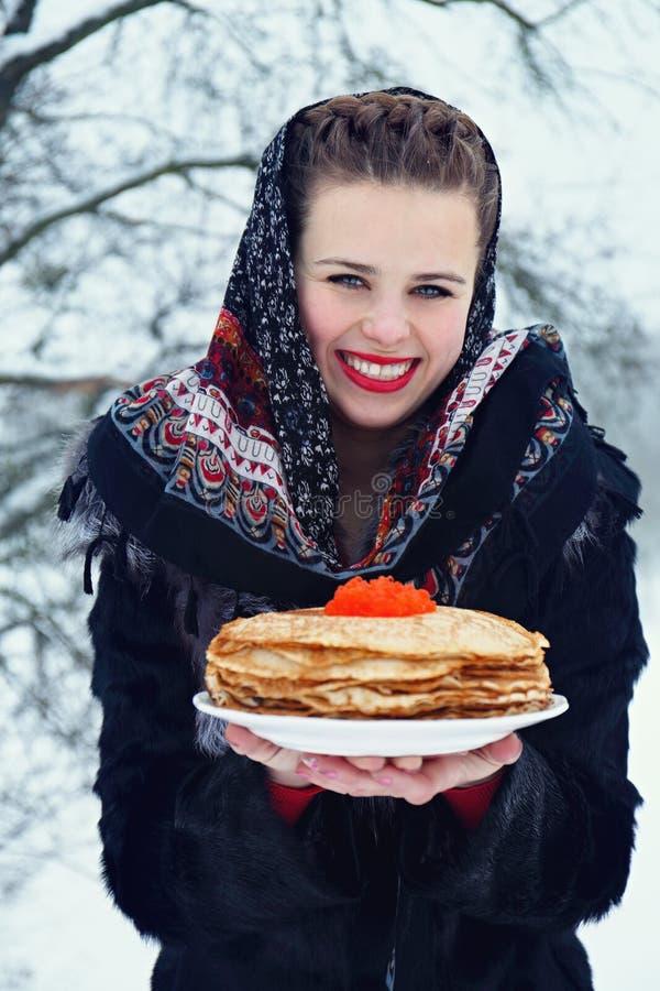 Kvinna med en platta av pannkakor royaltyfri foto