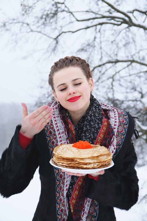 Kvinna med en platta av pannkakor och kaviaren royaltyfria bilder