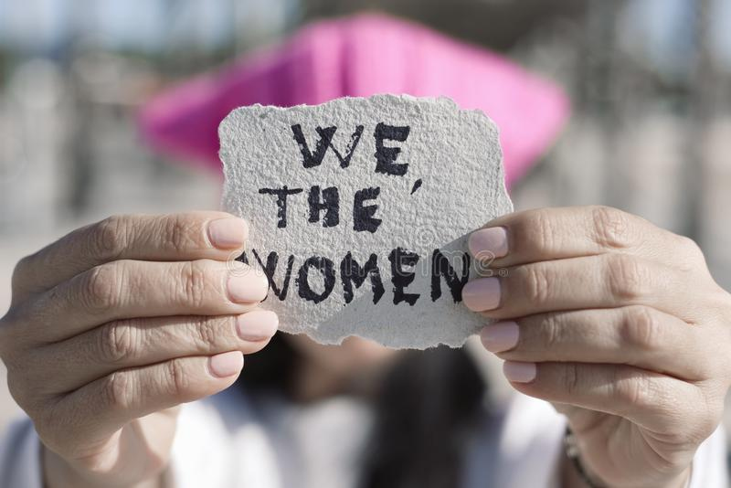 Kvinna med en pussyhat och texten oss kvinnorna fotografering för bildbyråer