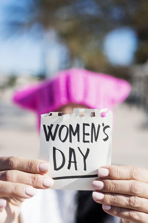 Kvinna med en rosa hatt och textkvinnornas dag arkivbild