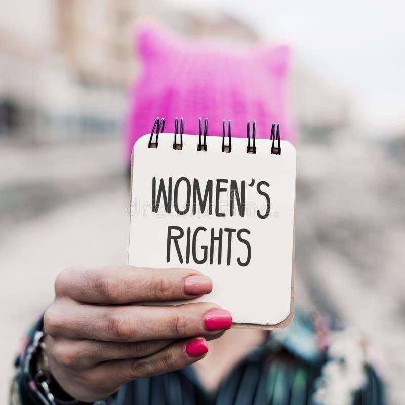 Kvinna med en rosa hatt och textkvinnornas rätter royaltyfria bilder
