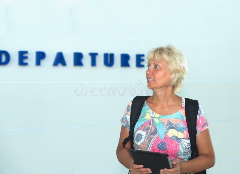 Kvinna med en ryggsäck och en elektronisk apparat arkivbild