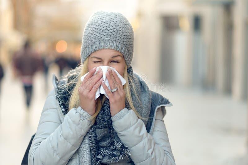 Kvinna med en säsongsbetonad vinterförkylning som blåser hennes näsa arkivfoto